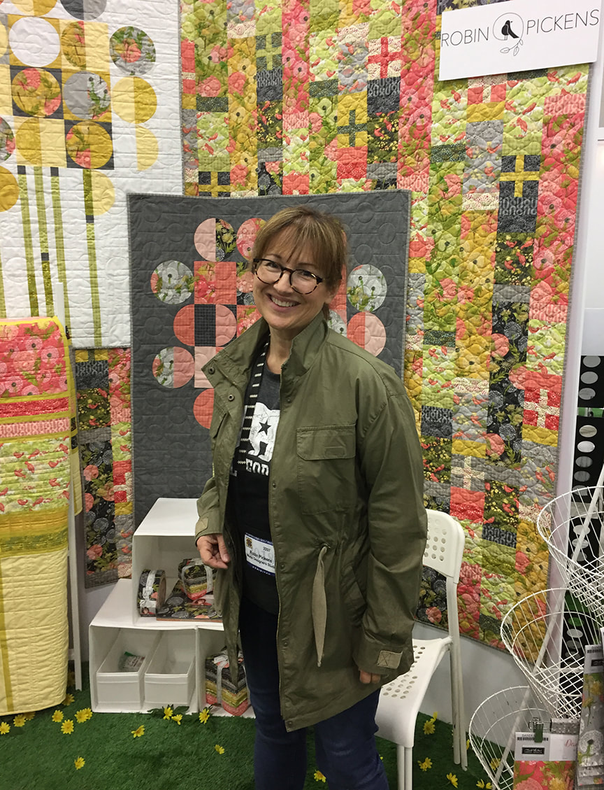 Robin Pickens at Portland Quilt Market after setting up booth at Moda with new Dandi Annie dandelion and birds line.